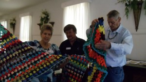 Ellen Whitley, J.D. Todd, and Mark Whitley look at the prayer shawls Todd made for them